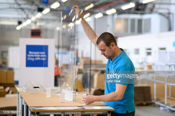 Member of the production team deconstructs a dividing screen for the mobile phone counters of the Tesco chain of supermarkets at the HL Display...