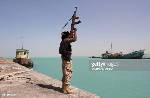 A member of the progovernment forces raises his weapon in the port of the western Yemeni coastal town of Mokha as they advance in a bid to try to...