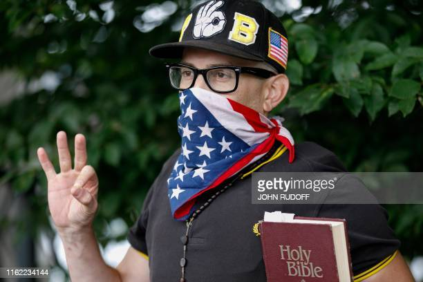 """Member of the """"Proud Boys"""" far-right group holds a bible and displays the OK hand gesture believed to have white supremacist connotations during """"The..."""