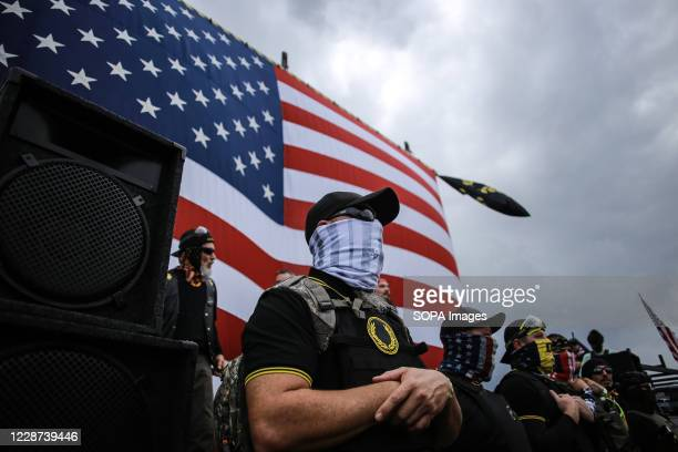 Member of the Proud Boys guards the front stage as another member of the proud boys gives a speech during the rally. Hundreds of members of the...