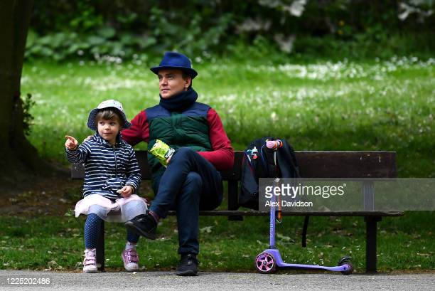 A member of the public and a young child relax in Kennington Park on May 16 2020 in London England The prime minister announced the general contours...