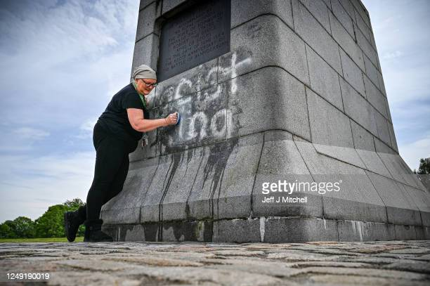 A member of the public cleans the Robert the Bruce Statue which has been defaced with graffiti saying Racist King on June 12 2020 in Bannockburn...