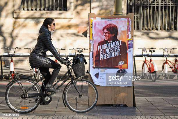 A member of the public cycles past an election poster for the forthcoming Catalan regional election showing the deposed Catalan president Carles...