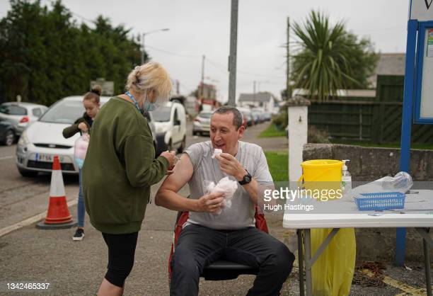 Member of the public eats candy floss from the nearby fairground while he receives a Pfizer Covid vaccination at an NHS walk-up vaccination unit...