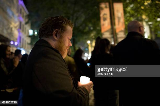 A member of the public holds a candle following a vigil on St Ann's Square in Manchester northwest England on May 29 exactly one week after a bomb...