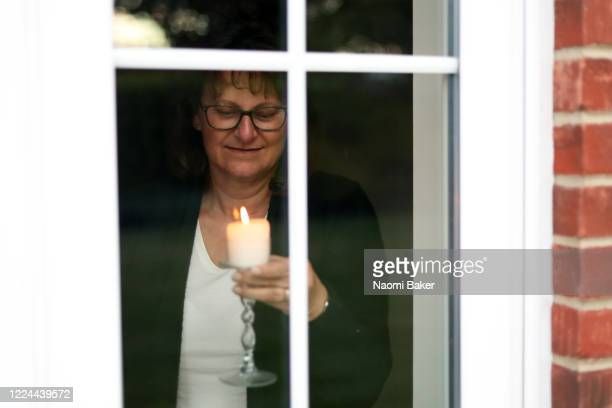 A member of the public holds up a candle in her window to celebrate the 200th Birthday of Florence Nightingale on May 12 2020 in Southampton England...