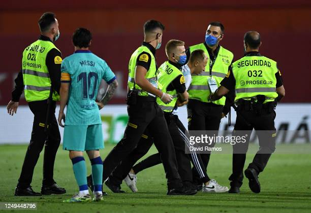 Member of the public is dragged away by security guards after invading the pitch during the La Liga match between RCD Mallorca and FC Barcelona at...