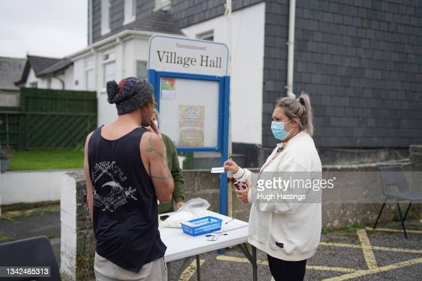 Member of the public is interviewed by NHS staff before receiving a Pfizer Covid vaccination at an NHS walk-up vaccination unit outside the village...