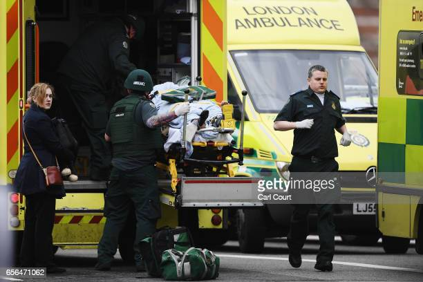 A member of the public is moved into an ambulance by emergency services near Westminster Bridge and the Houses of Parliament on March 22 2017 in...