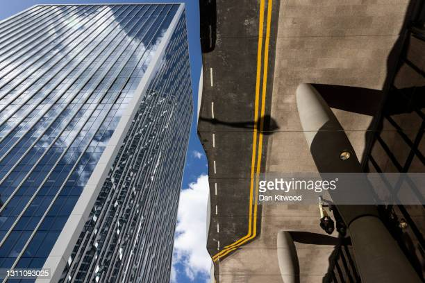 Member of the public is reflected in the mirrored roof of an office building in the Canary Wharf business district on April 06, 2021 in London,...