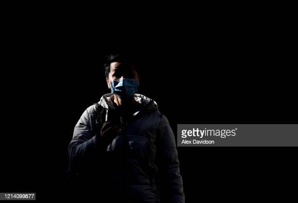 A member of the public is seen wearing a protective mask on March 22 2020 in London England Coronavirus has spread to at least 188 countries claiming...