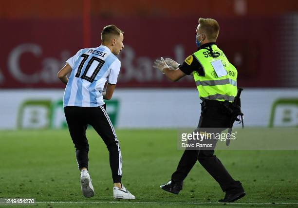 A member of the public is tackled by a security guard after invading the pitch during the La Liga match between RCD Mallorca and FC Barcelona at...