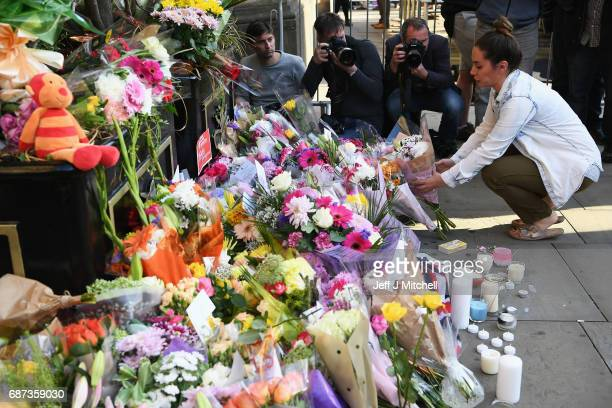 A member of the public lays flowers at a candlelit vigil to honour the victims of Monday evening's terror attack at Albert Square on May 23 2017 in...