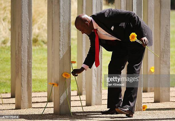 Member of the public lays flowers at the 52 steel pillars memorial to the victims of the July 7 2005 London bombings in Hyde Park on July 7 2015 in...