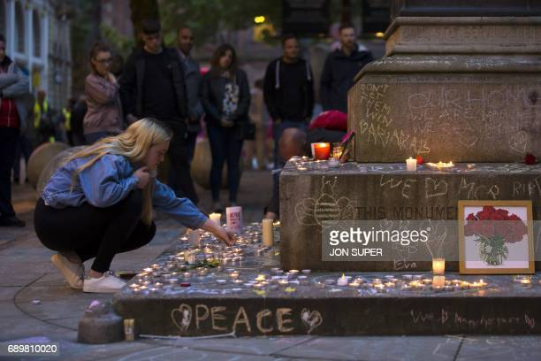 A member of the public lights memorial candles before a vigil in St Ann's Square in Manchester north west England on May 29 placed in tribute to the...