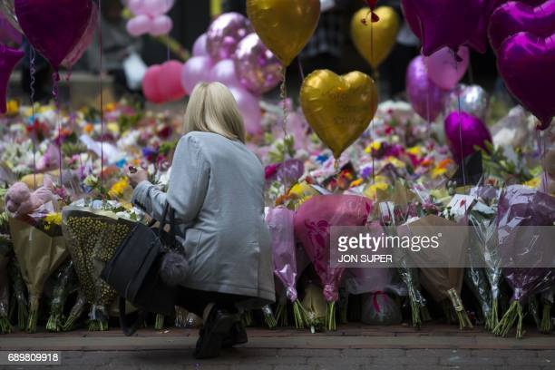 A member of the public looks at the balloons and flowers before a vigil in St Ann's Square in Manchester north west England on May 29 placed in...