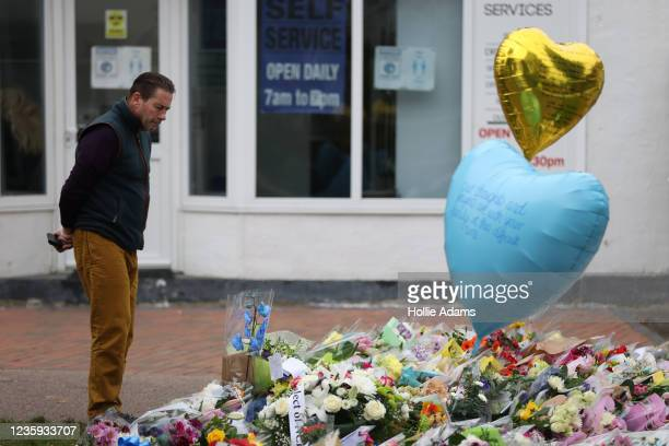 Member of the public looks at the floral tributes laid in memory of David Amess MP near Belfairs Methodist Church on October 17, 2021 in...