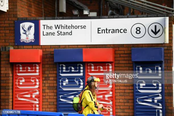 Member of the public passes the Whitehorse Lane Stand at a temporary centre set up at Selhurst Park football stadium, home ground of English Premiere...