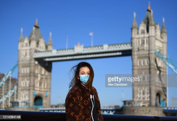 A member of the public poses for a photo in front of Tower Bridge whilst wearing a protective mask on March 22 2020 in London England Coronavirus has...