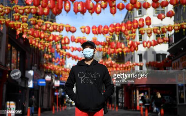 A member of the public poses for a photo whilst wearing a protective mask in Chinatown on March 21 2020 in London England Coronavirus has spread to...