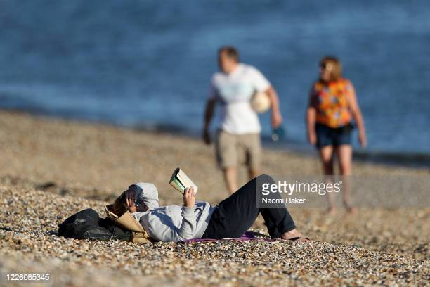 Member of the public reads a book on the beach on May 20, 2020 in Lee-On-The-Solent, England . The British government has started easing the lockdown...