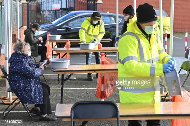 Member of the public reads an instruction sheet before taking a coronavirus test at a temporary COVID-19 testing facility, part of surge testing for...
