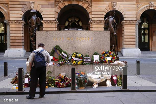 A member of the public reads messages on the wreaths laid on The Cenotaph Martin Place on April 25 2020 in Sydney Australia Traditional Anzac Day...
