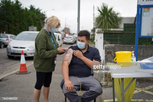 Member of the public receives a Pfizer Covid vaccination at an NHS walk-up vaccination unit outside the village hall on September 25, 2021 in the...