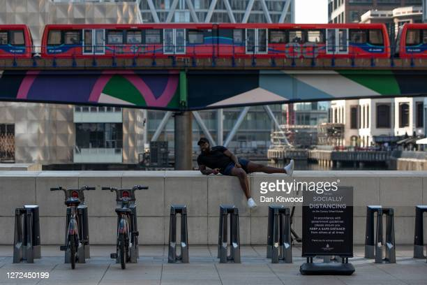 Member of the public relaxes on a wall in the Canary Wharf business district on September 14, 2020 in London, England. Many companies with...