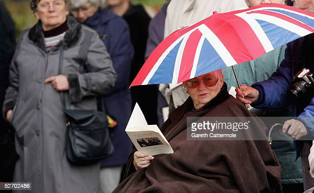 A member of the public shields herself from the elements in the grounds of The Parish Church of Saint Mary the Virgin as the funeral of Sir John...