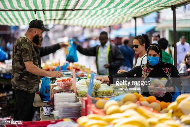 Member of the public shops for fruit and vegetables at Walthamstow Street Market on May 26, 2020 in London, England. The British government continues...