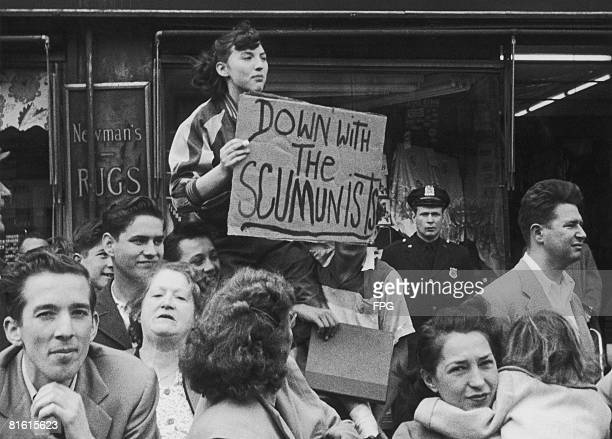 A member of the public shows her disapproval of a Communistsponsored May Day Parade in New York City with a handwritten 'Down with the Scumunists'...