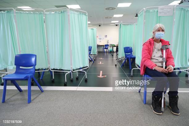 Member of the public sits in the waiting area after receiving a doser of the Moderna Covid-19 vaccine at a vaccination centre at Ffwrnes Theatre in...