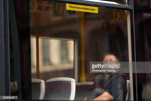 Member of the public sitting in a bus wears a pandemic face mask ahead of the prime minister announcing the government's Covid-19 winter strategy on...