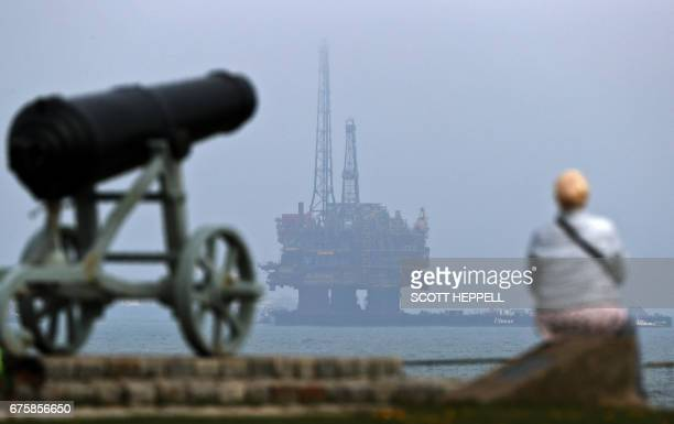 A member of the public stands on the shoreline looking out to sea as Shell's Brent Delta Topside offshore oil drilling rig platform is towed by tug...