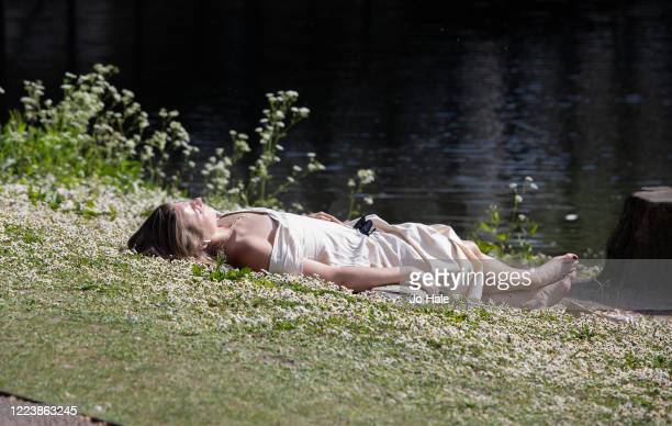 Member of the public sunbathes by a bridge on a warm, sunny afternoon in Regent's Park on May 09, 2020 in London, United Kingdom. The country...