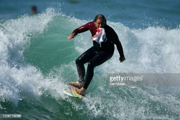A member of the public surfs into shore to dispose of a piece of waste plastic he found in the sea at Fistral Beach on May 24 2020 in Newquay England...