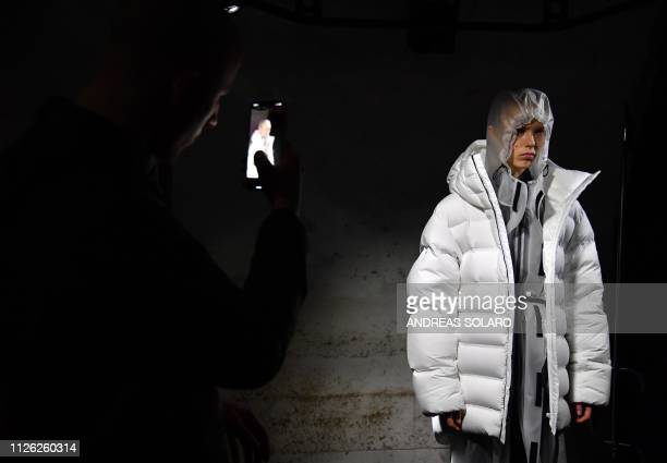A member of the public takes a photo of a model during a still presentation of the Moncler women's Fall/Winter 2019/2020 collection fashion show on...