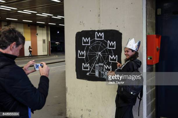 A member of the public takes a photograph a woman wearing a foil crown next to a new work by street artist Banksy on a wall by the Barbican Centre on...