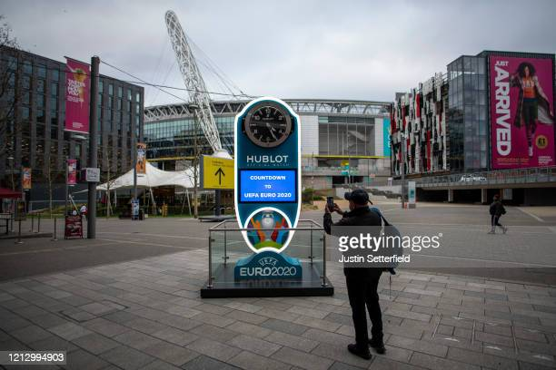 Member of the public takes a picture of the Euro 2020 countdown clock at Wembley Stadium on March 17, 2020 in London, England. Euro 2020 has been...