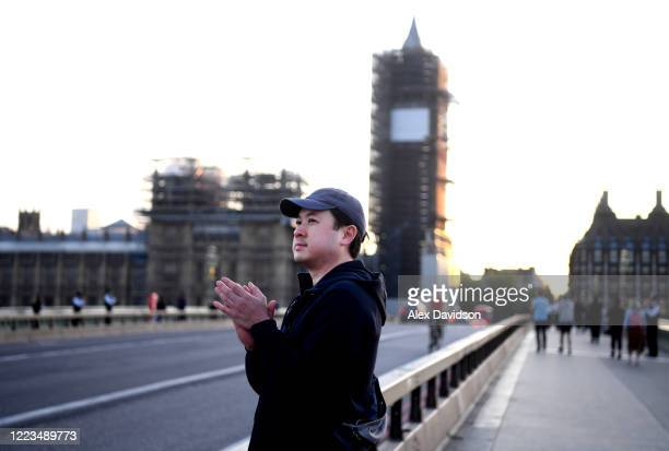 A member of the public takes part in the applause on Westminster Bridge on May 07 2020 in London England United Kingdom Following the success of the...
