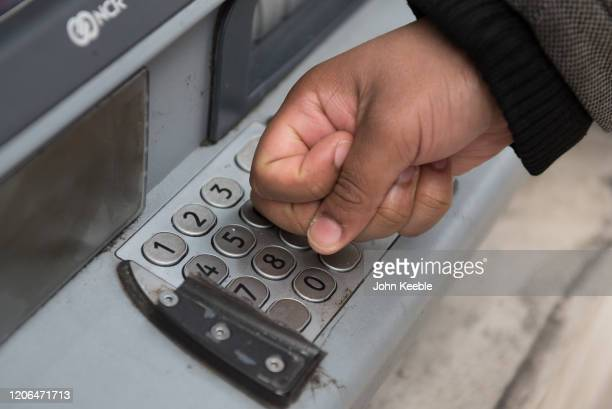 A member of the public touches a keypad at a cash machine with his knuckles rather than his finger tips to limit the risk of contracting the...