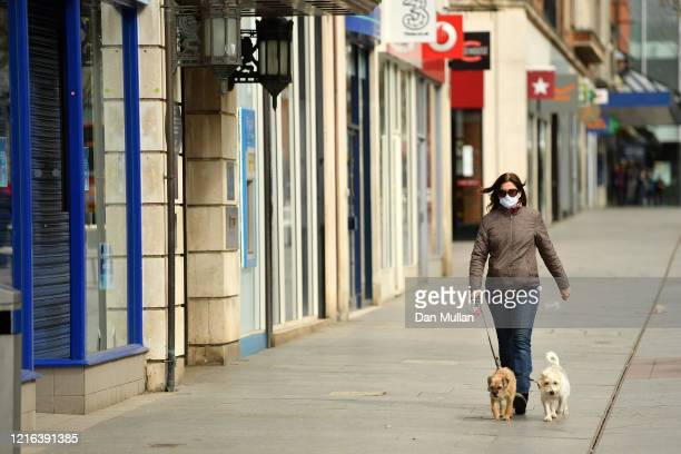 A member of the public walks her dogs down an empty high street in the city centre on April 02 2020 in Exeter England The Coronavirus pandemic has...