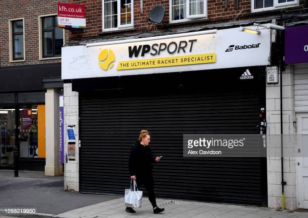 A member of the public walks past a closed Tennis Racket shop on June 29 2020 in Wimbledon England The Wimbledon Tennis Championships were due to...
