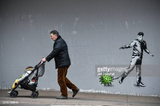 Member of the public walks past a coronavirus mural on a building in Bath Street on April 4, 2020 in Glasgow, Scotland. The Coronavirus pandemic has...
