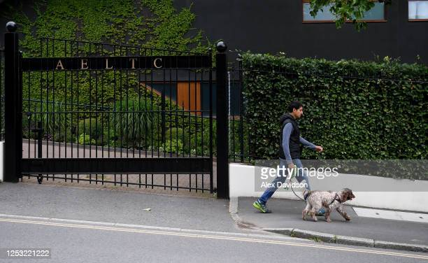 A member of the public walks past a gate at The All England Tennis and Croquet Club on June 29 2020 in Wimbledon England The Wimbledon Tennis...