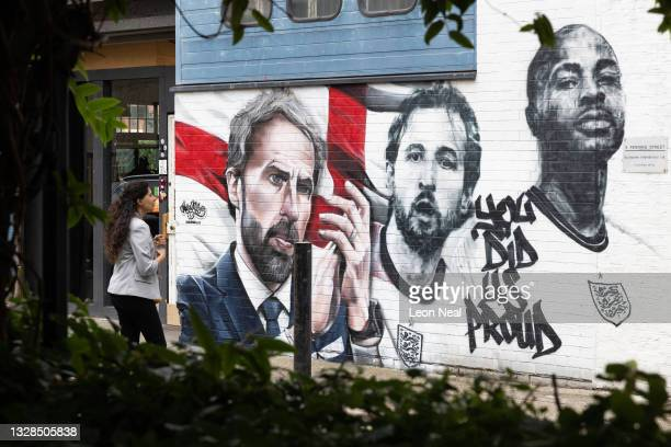 Member of the public walks past a new mural honouring members of the England football team, on July 13, 2021 in London, England. The mural of Gareth...
