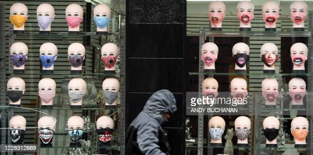 TOPSHOT A member of the public walks past a shop selling face masks for the COVID19 pandemic in Glasgow on September 2 2020 The Scottish government...