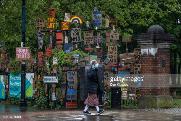 Member of the public walks past an display of signs put there by local artist Peter Liversidge on April 28, 2020 in London, United Kingdom . British...