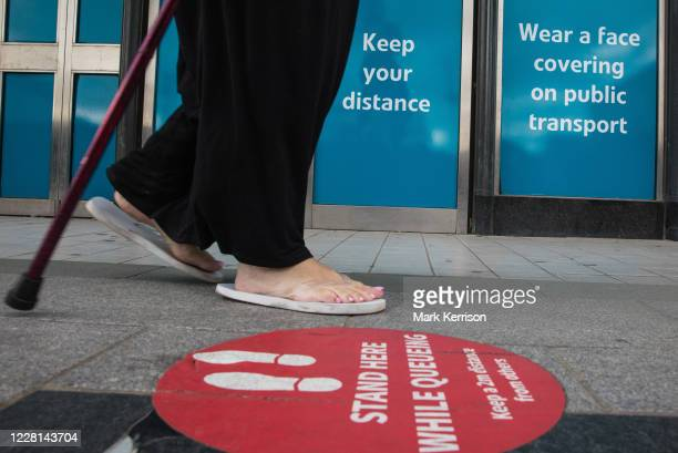 Member of the public walks past COVID-19 post lockdown public information displays on 21st August 2020 in Slough, United Kingdom. Slough has been...